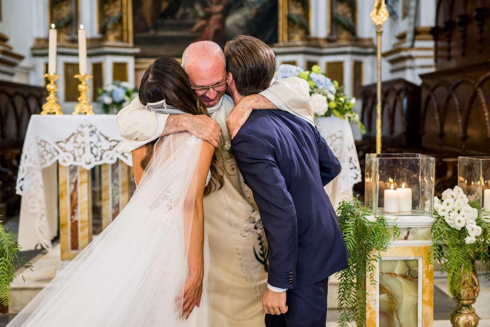 il prete si abbracia gli sposi